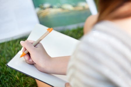 Close-up of a girl writing in a notebook photo