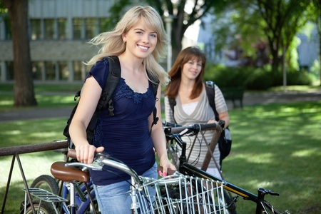 woman bike: College students standing with bicycle on college campus lawn Stock Photo