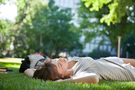 laying down: Young college student lying down on grass at campus lawn
