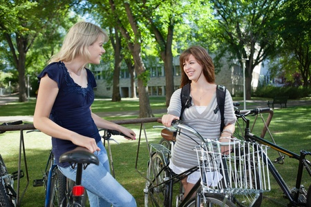 Happy young female students standing with bicycle at college campus lawn photo