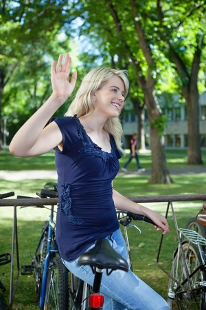 greets: College student waving hand at someone while standing near by her bike Stock Photo