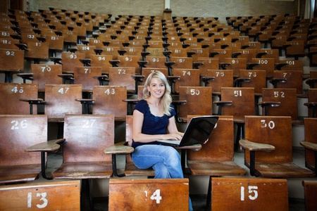 Portrait of young college student using laptop at university hall photo