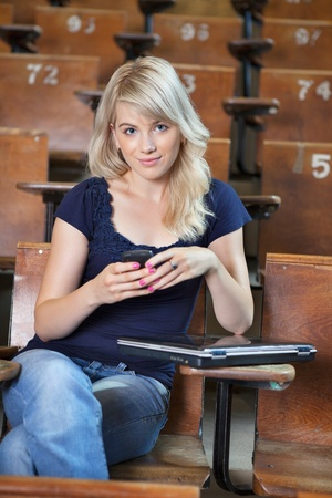 Portrait of young happy college girl sending a text message photo