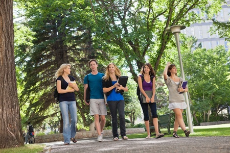 college class: University students walking through the park on their way to college