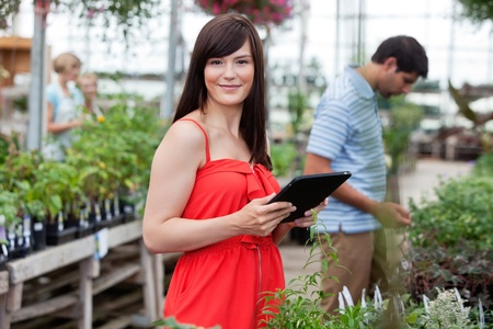 Attractive woman holding tablet pc with people in background photo