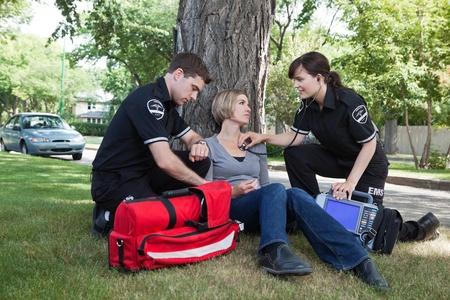 accident rate: M�dica de emergencia profesionales evaluar a un paciente herido en la calle Foto de archivo