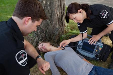 accident rate: Los trabajadores de emergencia Mujer escuchar latidos del coraz�n de la mujer enferma Foto de archivo