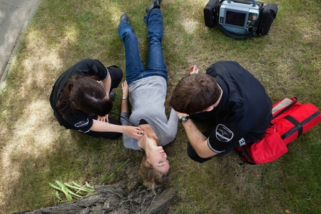 Emergency medical team responding to a woman in a park Stock Photo - 10762619
