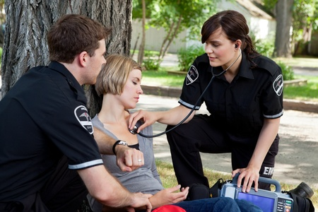 Emergency medical professionals assessing an injured patient Stock Photo - 10762469