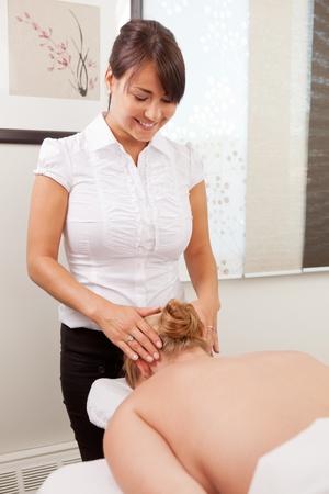 acupuncturist: Acupunturista Mujer masaje de la cabeza del paciente en preparaci�n para la acupuntura. Foto de archivo