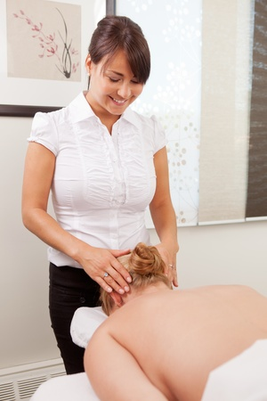Female acupuncturist massaging head of patient in preparation for acupuncture. photo