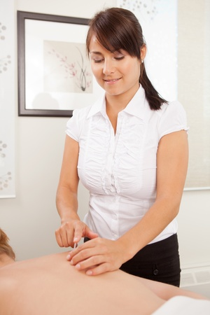 acupuncturist: Acupunturista mujer que usa un tubo de inserci�n para colocar una aguja en un paciente de sexo femenino. Foto de archivo
