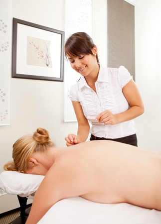 filiform: A woman acupuncturist performing a back treatment on a female pasient.