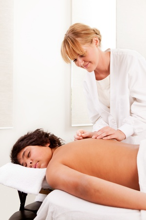 acupuncturist: Young male acupuncture patient receiving treatment on back