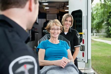 Portrait of a healthy senior citizen on an ambulance stretcher photo