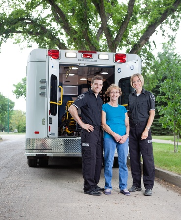 paramedic: Portrait of patient with ambulance staff outside vehicle