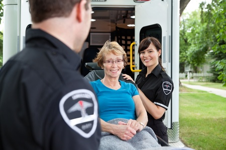 Two ambulance workers pushing a happy femaile patient photo