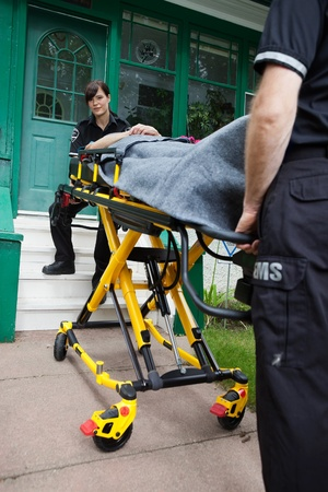 Ambulance workers with a stretcher outside a house Stock Photo - 10789791