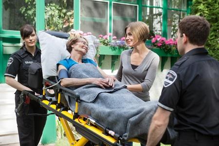 paciente en camilla: Mujer mayor con un familiar al lado de ser llevado al hospital