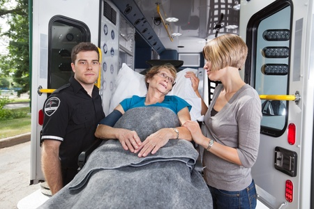cfr: Senior woman being taken on ambulance, daughter at side Stock Photo