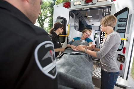 Senior woman being loaded onto ambulance with caregiver at side