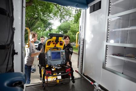 paciente en camilla: Equipo de emergencia de la carga de pacientes en ambulancia, el m�dico de al lado Foto de archivo