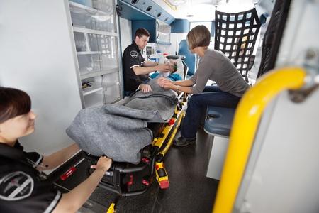 urgencias medicas: Equipo médico de emergencia atendiendo a los pacientes de alto nivel en la ambulancia, el médico de al lado