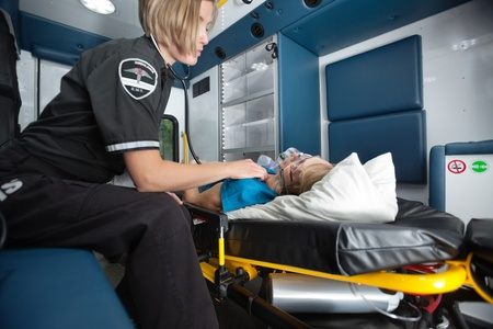 paramedic: Senior woman receiving emergency medical care in ambulance