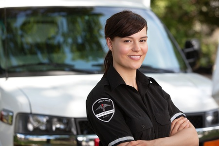 emt: Portrait of a happy friendly female paramedic standing in front of ambulance Stock Photo