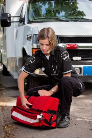 paramedic: Servicios médicos de emergencia professioanl la apertura de una unidad de oxígeno portátil cerca de una ambulancia