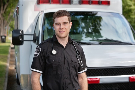 Portrait of young paramedic standing in front of white ambulance photo