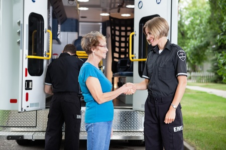 Ambulance staff shaking hands with elderly patient photo
