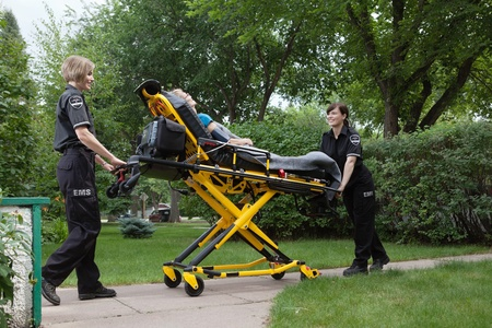 transporting: Female emergency medical team transporting senior patient on stretcher Stock Photo
