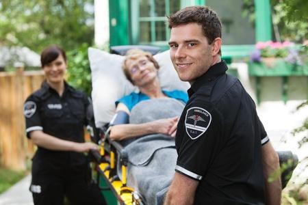 paciente en camilla: Profesionales ambulancia varones con una mujer feliz altos en camilla