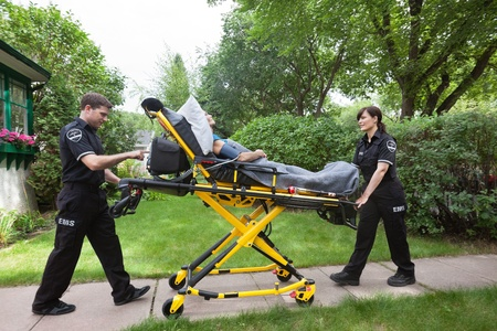 Senior woman on emergency medical stretcher being transported from home Stock Photo