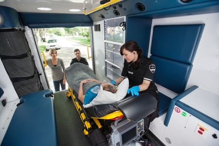 respond: Elderly woman loaded in ambulance being given oxygen Stock Photo