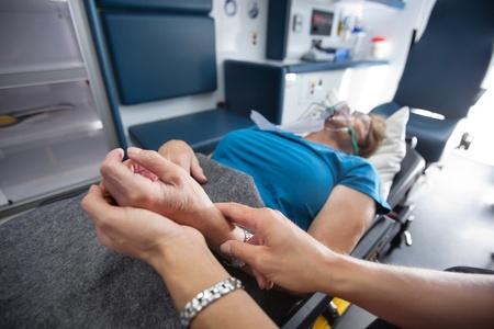 Detail van EMT werknemer te meten puls op senior vrouw de patiënt in de ambulance