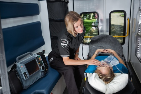 paramedics: Female EMT worker tending to ill senior patient, listening to heart rate with stethoscope Stock Photo