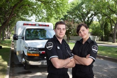 Retrato de dos paramédicos de pie en la parte delantera del vehículo ambulancia