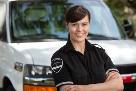 ambulance car: Portrait of a happy confident woman paramedic standing in front of ambulance