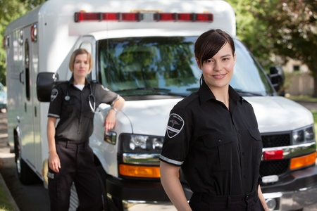 Emergency medical workers standing with ambulance photo