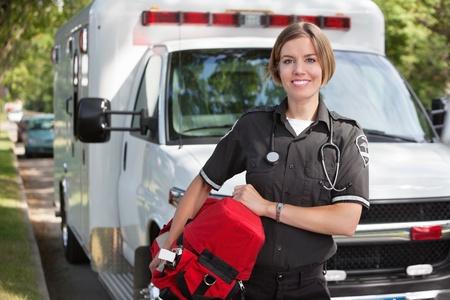 ambulancia: Retrato de un paramedica feliz llevando una unidad portátil de oxígeno Foto de archivo