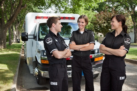 cfr: Group of 3 EMS workers standing in front of ambulance visiting Stock Photo