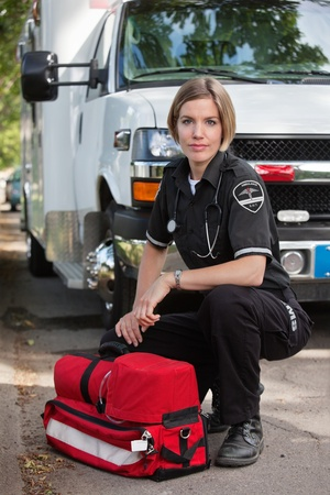 emergency services: Confident EMS paramedic kneeling by portable oxygen unit and ambulance Stock Photo