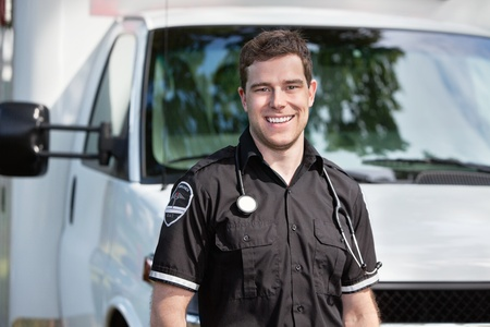 Portrait of happy smiling man paramedic in front of ambulance photo