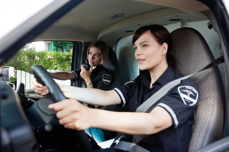 response: Female EMT calling dispatcher on radio - shallow depth of field, focus on woman with radio Stock Photo