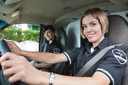 cfr: Portrait of happy female paramedic driving ambulance with team member in background Stock Photo