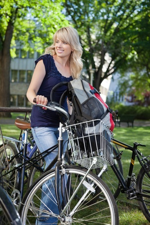 Beautiful blonde female student standing with her bike and looking away photo