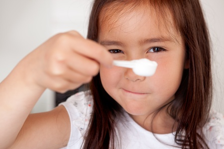 a level: Young girl measuring baking ingredient, holding spoon up to eye