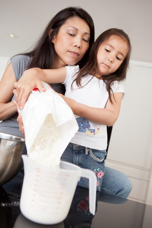 Mother and daughter baking together, measuring out dry ingredient Stock Photo - 10988921